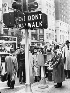 It was not until in 1955, though, that a new kind first appeared on the streets of the city. It was a rather bulky, not to mention very heavy, pedestrian signal that was manufactured by the Winko-Matic company, and its illumination source was neon as well. Below, is a photograph from 1955 that shows a newly installed (then) pair at the corner of 7th Avenue and W. 35th Street. In the photograph, then traffic commissioner T.T. Wiley (handling the signal controller below the pair) activates the signals for the first time, while a group of fellow New Yorkers around him watch. The first 300 were installed in Manhattan, while others would spread throughout the rest of the boroughs in later years. From what is known, New York City installed these pedestrian signals until the early 1970s. At least two other kinds from possibly the Winko-Matic company were installed in the 1960s and 1970s in certain locations of the city, and these remained in service until the early 1980s.