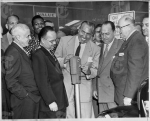 Acting President of the City Council Joseph T. Sharkey dropping the first coin into the gadget on the south side of 125th Street between Lenox and Seventh Avenues. Looking on at the ceremony are, left to right, Spencer C. Young, City Treasurer; T. T. Wiley, Acting Traffic Commissioner; Police Commissioner George P. Monaghan and Col. Leopold Philipp, president of the Uptown Chamber of Commerce. In the backgrouond at the left in a checkered shirt is middleweight boxcing champioin, Ray Robinson. (NY Times)